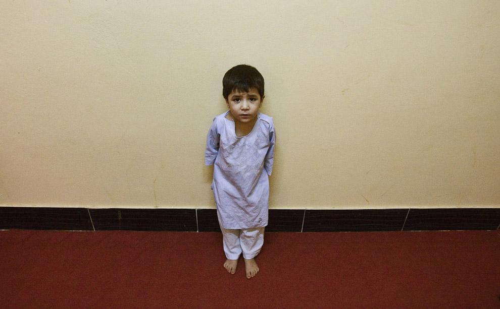 Сын афганской женщины-заключенной стоит в коридоре тюрьмы в Герате