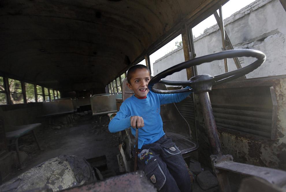 Афганский мальчик в уничтоженном старом советском автобусе в Кабуле