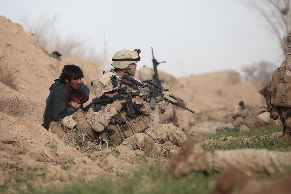 Американские морские пехотинцы и отец с ребенком, который бежал из дома после того, как талибы открыли огонь в городе Марджа в провинции Гильменд