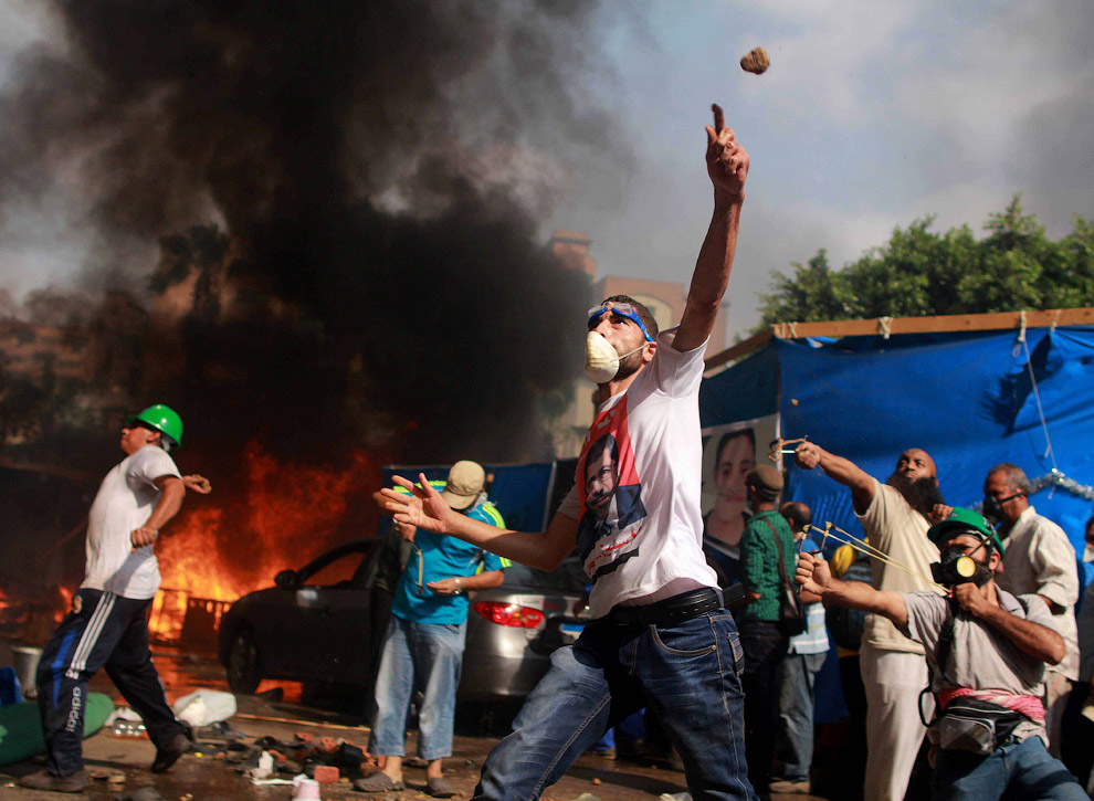 Египетские протестующие забрасывают камнями военных во время зачистки площадей в Каире от палаточных городков