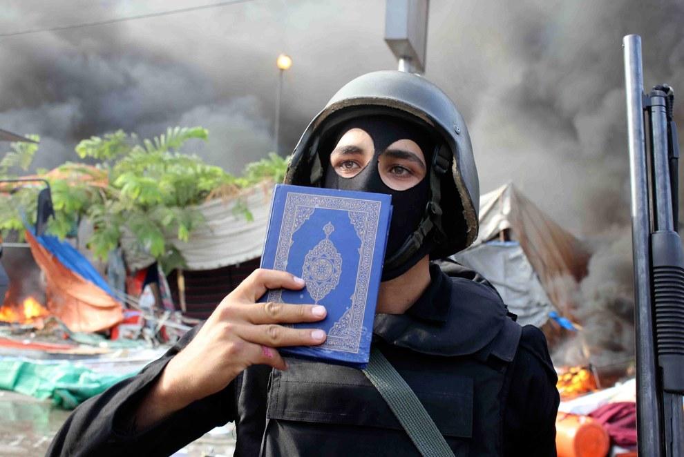 Сотрудница сил безопасности воздействует на протестующих с помощью Корана