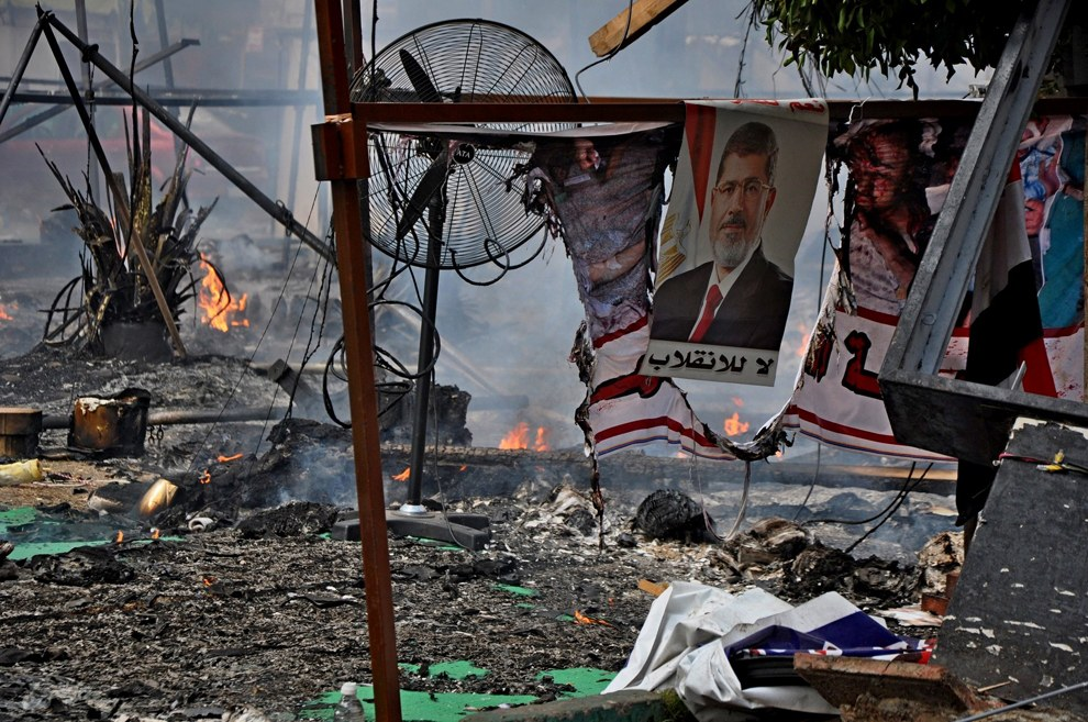 Плакат с экс-президентом Мурси на месте разогнанного лагеря протестующих в Каире, Египет, 14 августа 2013