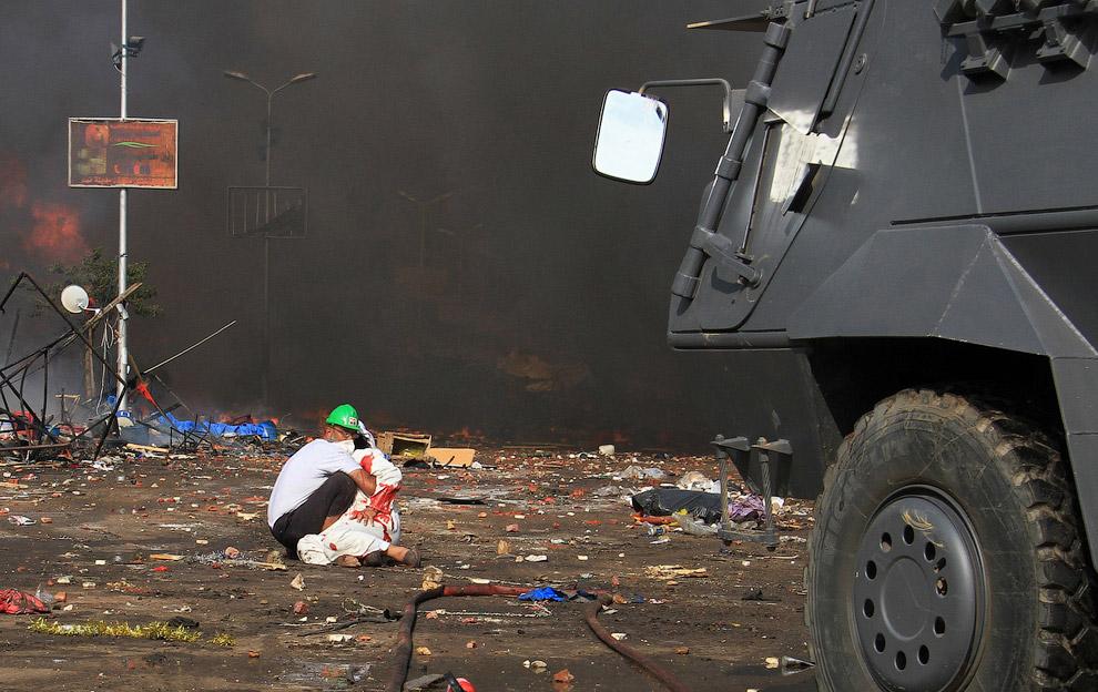 Сторонник свергнутого президента Мохаммеда держит раненого при разгоне палаточных городков