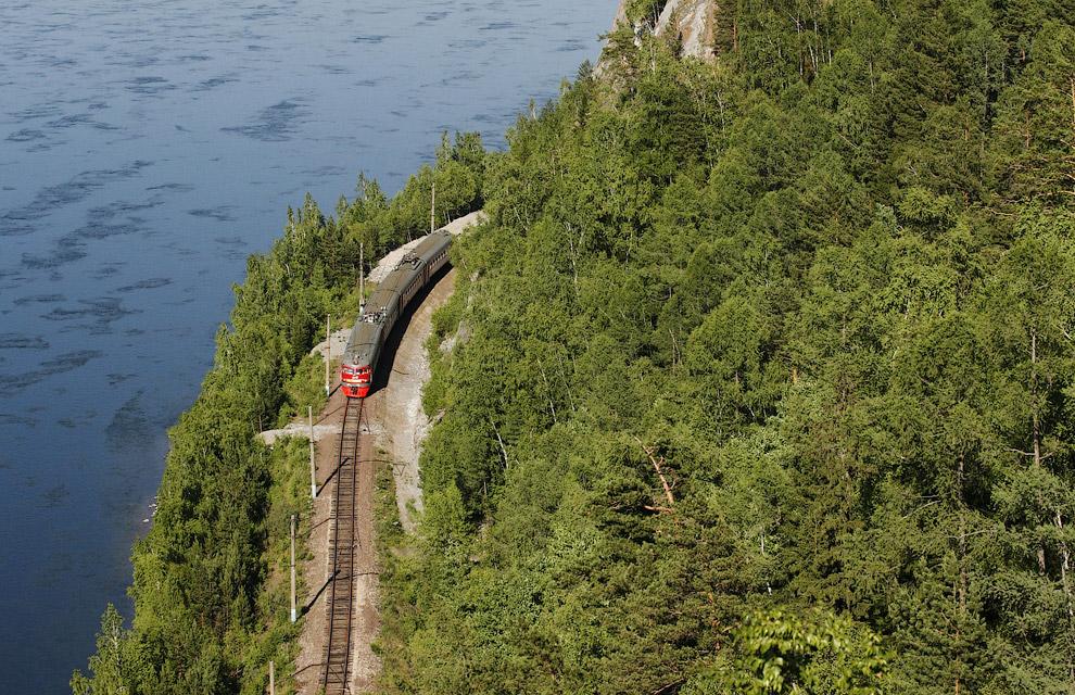 Пассажирский поезд движется по берегу Енисея, вблизи деревни Слизнево