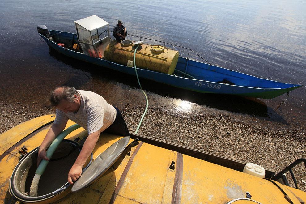 Самодельный молоковоз — моторная лодка. Водитель грузовика перекачивает насосом молоко в свою емкость
