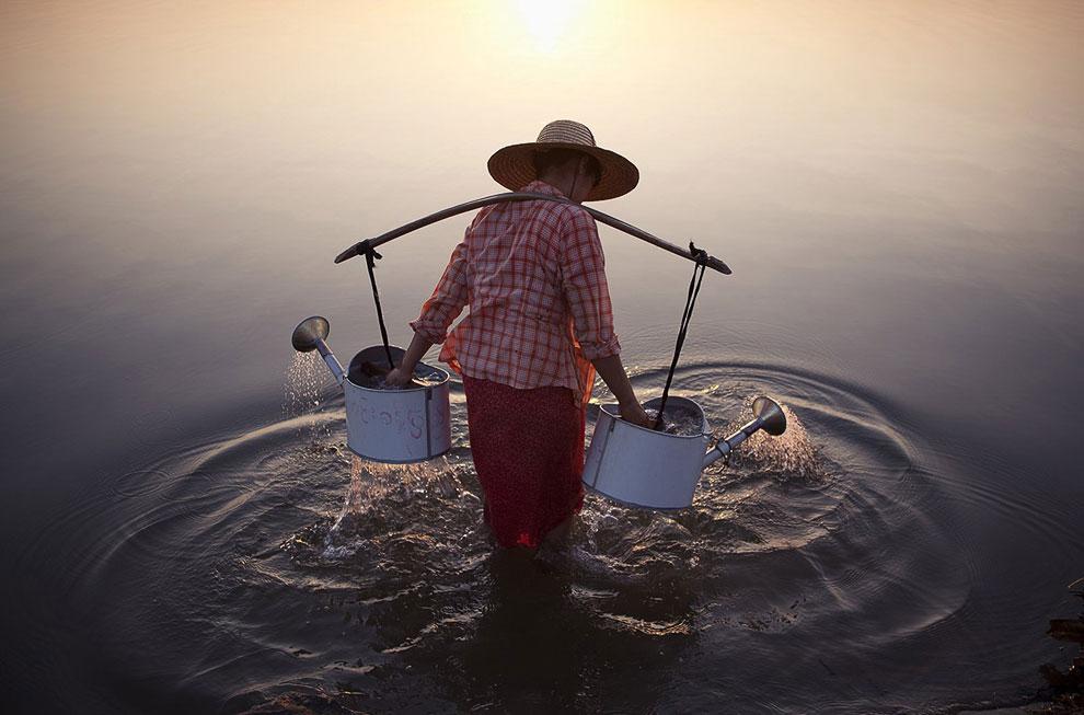 Женщина набирает воду домой