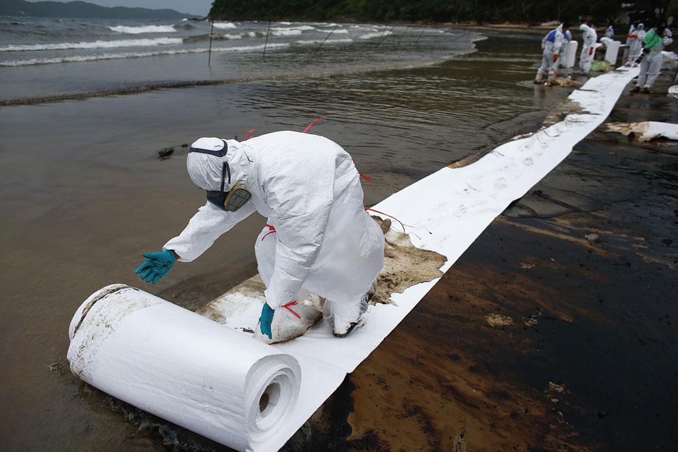 Солдаты разматывают на побережье специальную впитывающую бумагу