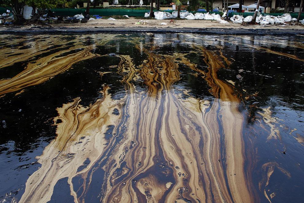 Нефтяные полосы на пляже Ао Прао острова Самет, Таиланд