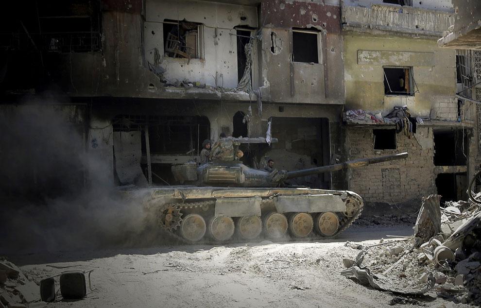 Бойцы правительственных войск патрулируют город Хомс на танке