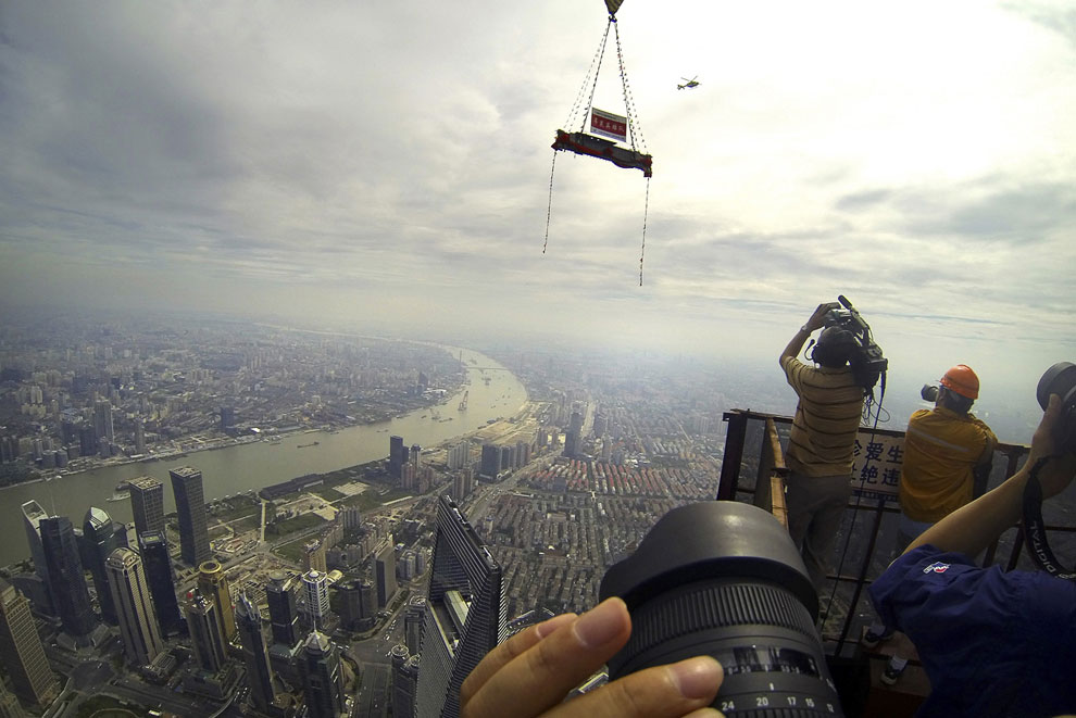 Подъемный кран поднимает вверх деталь от Шанхайской башни