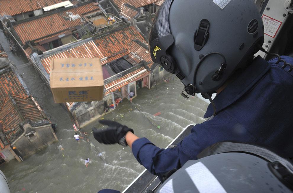 Спасатель сбрасывает с вертолета ящик с питьевой водой