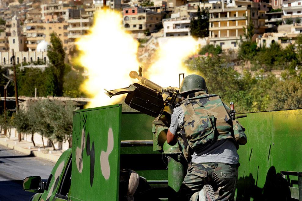 Солдат сирийской армии стреляет из крупнокалиберного пулемета во время стычки с мятежниками