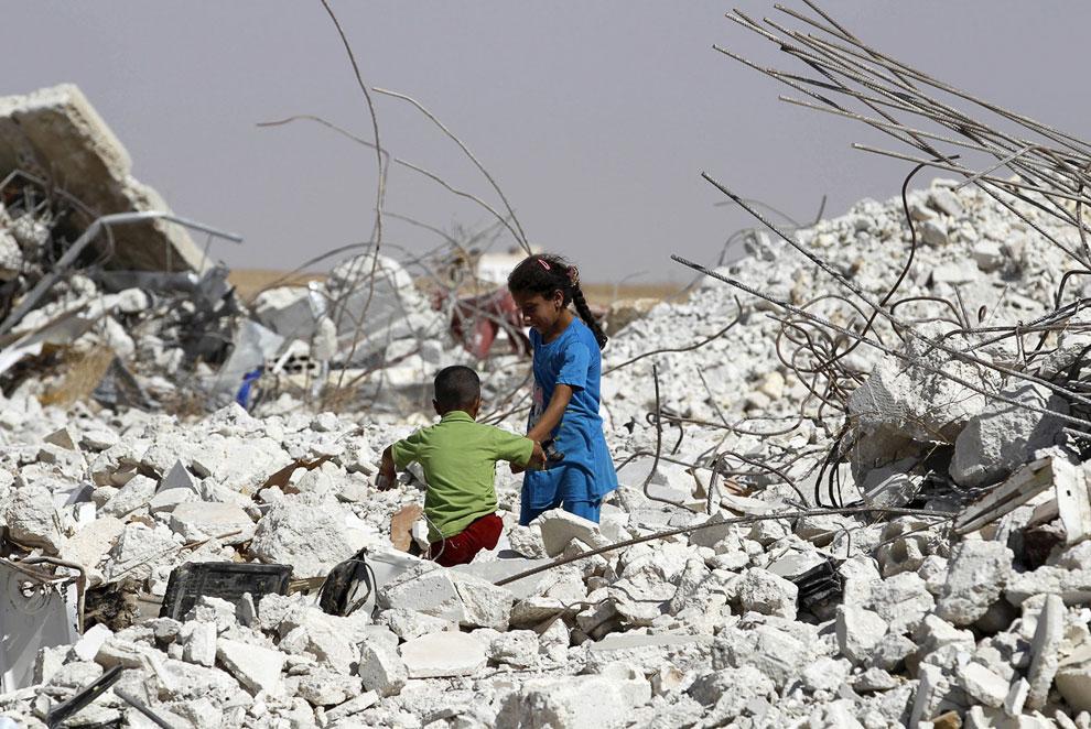 Девочка с братом пробираются через завалы разрушенного дома в городе Хама