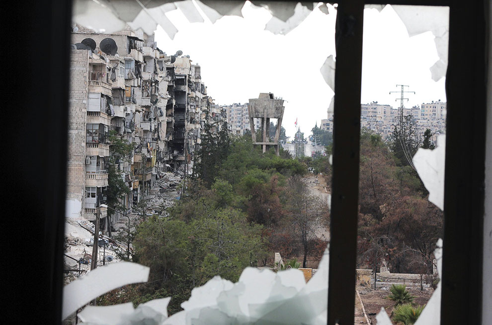 Вид на разрушенные здания из разбитого окна в Алеппо