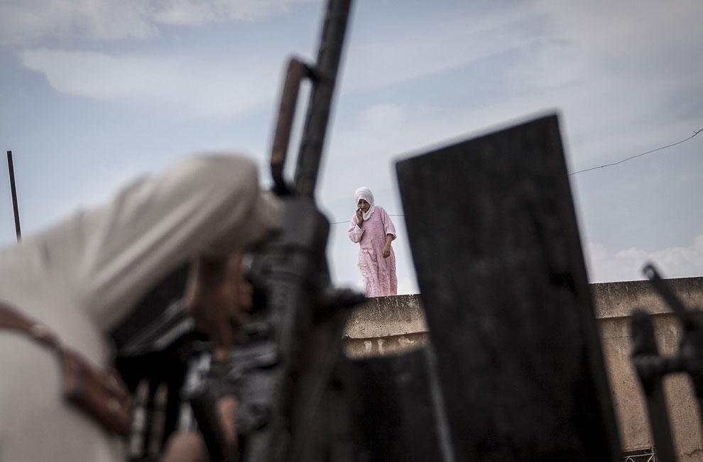 Сирийский девушка на крыше дома и готовящийся к бою боевик оппозиции