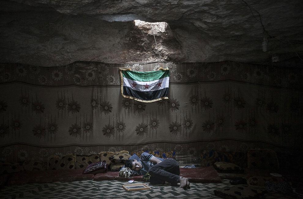Один из боевиков устал от стрельбы, отдыхает в лагере повстанцев, провинция Идлиб