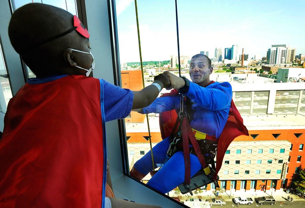 Мойщики окон, одетые в костюмы супергероев, удивляют детей в больнице во время своей работы