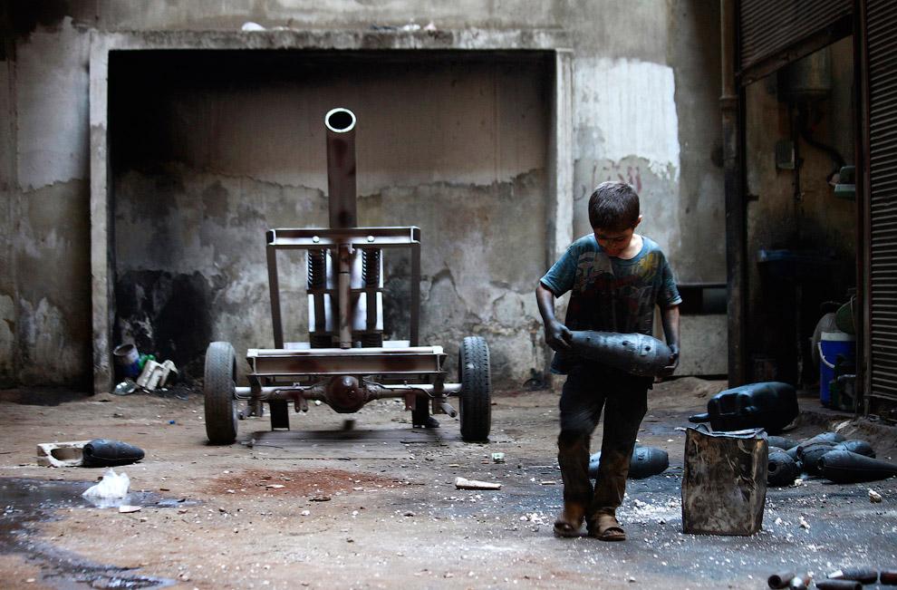 10-летний мальчик тащит минометный снаряд, Алеппо