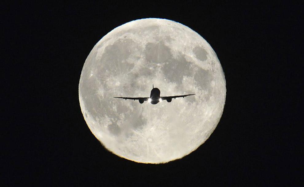 Полная луна и посадка самолета в аэропорту Хитроу на западе Лондона