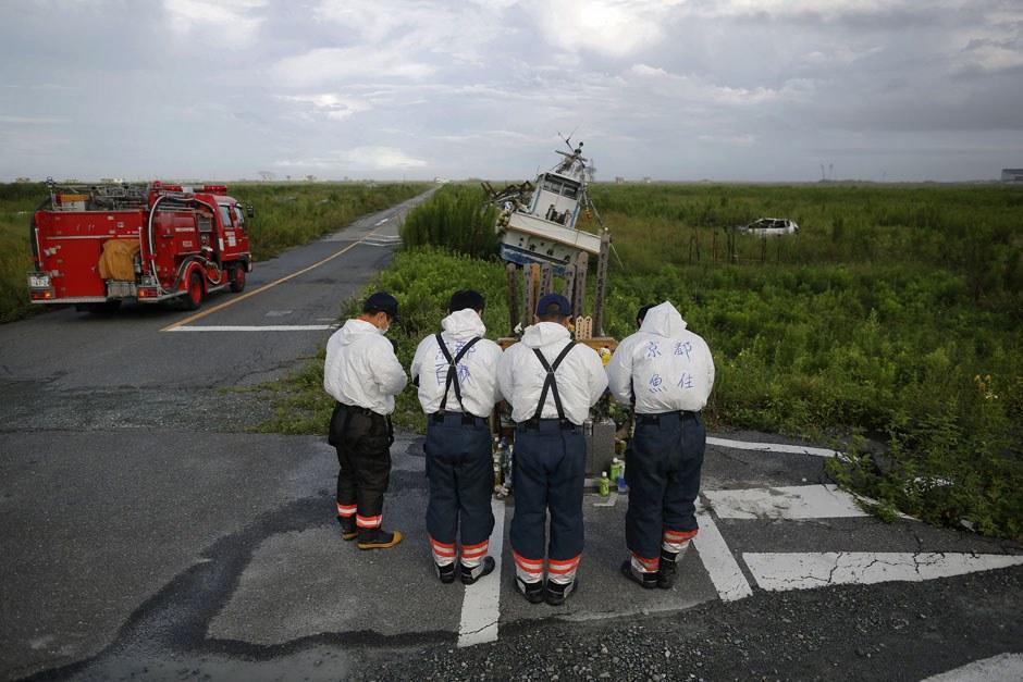 Пожарные из Киото у еще одного небольшого памятника жертвам землетрясения и цунами