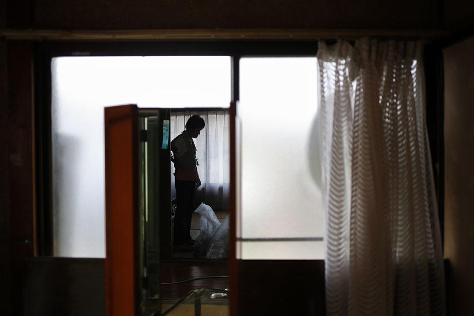62-летняя жительница, получившая специальное разрешение на посещение города-призрака Намие, ищет в своем бывшем доме вещи