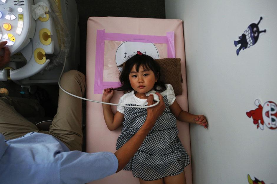 Врач проводит обследование щитовидной железы у 4-летней девочки в городе Иваки