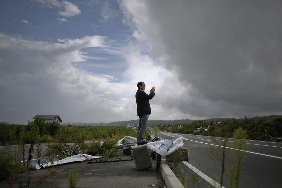 Приезжий из Хоккайдо делает снимки уничтоженных цунами прибрежных районов в городе Намие