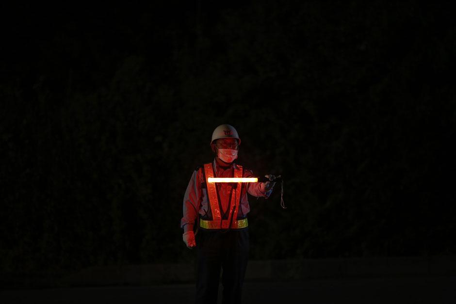 Сотрудник службы безопасности блокирует проезд в зону отчуждения вокруг АЭС «Фукусима-1»