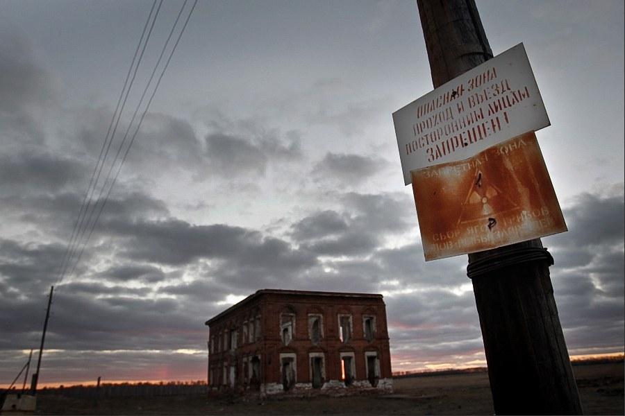 Село-призрак Муслюмово в Челябинской области. На фотографии: заброшенная школа и предупреждающий о радиации знак