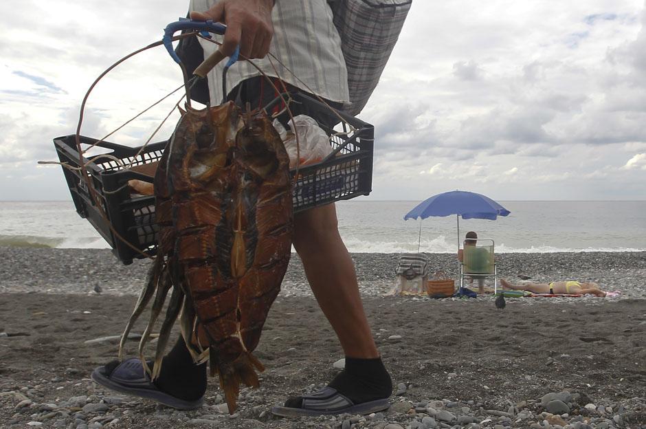 Продавец копченой рыбы на пляже