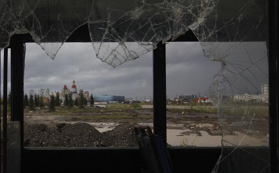 Вид на Олимпийские сооружения и жилые кварталы через окно заброшенного старого автобуса неподалеку