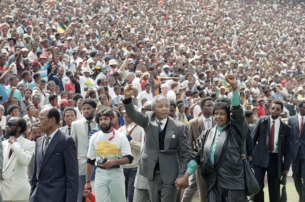 Только что освободившихся Нельсон Мандела входит на футбольный стадион Соуэто в Южной Африке, чтобы произнести речь. Его пришли послушать 120 000 человек