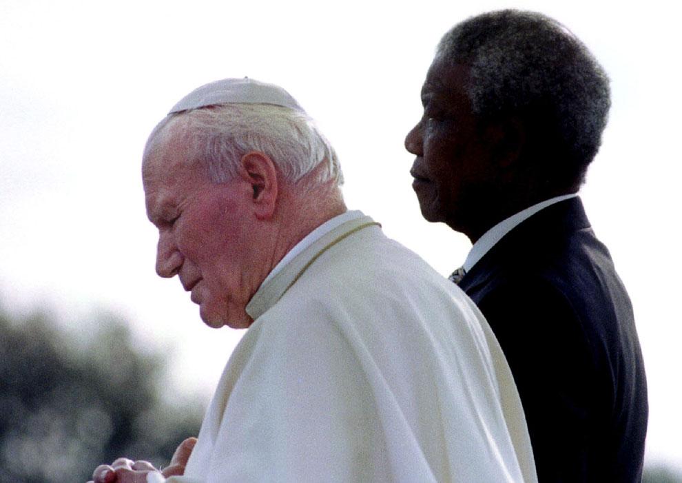 Президент ЮАР Нельсон Мандела и Папа Иоанн Павел II слушают государственный гимн в международном аэропорту Йоханнесбурга во время первого официального визита Папы в страну
