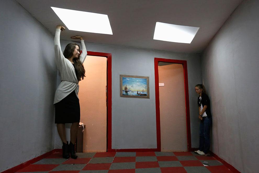 Посетители в комнате Эймса на частной выставке оптических иллюзий в Санкт-Петербурге