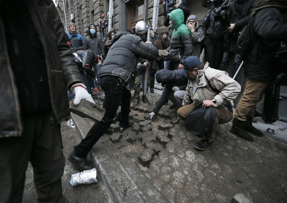 Так называемые оппозиционеры или провокаторы разбирают плитку для бросания камнями в полицейских