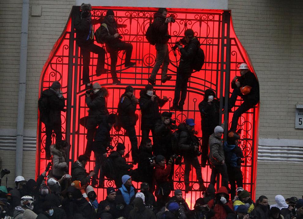 Люди в масках лезут на ворота возле здания администрации президента во время митинга сторонников интеграции с ЕС в Киеве