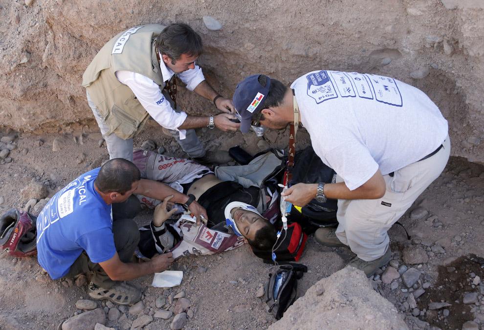 Медики оказывают помощь травмированному испанскому гонщику Gilbert Escale