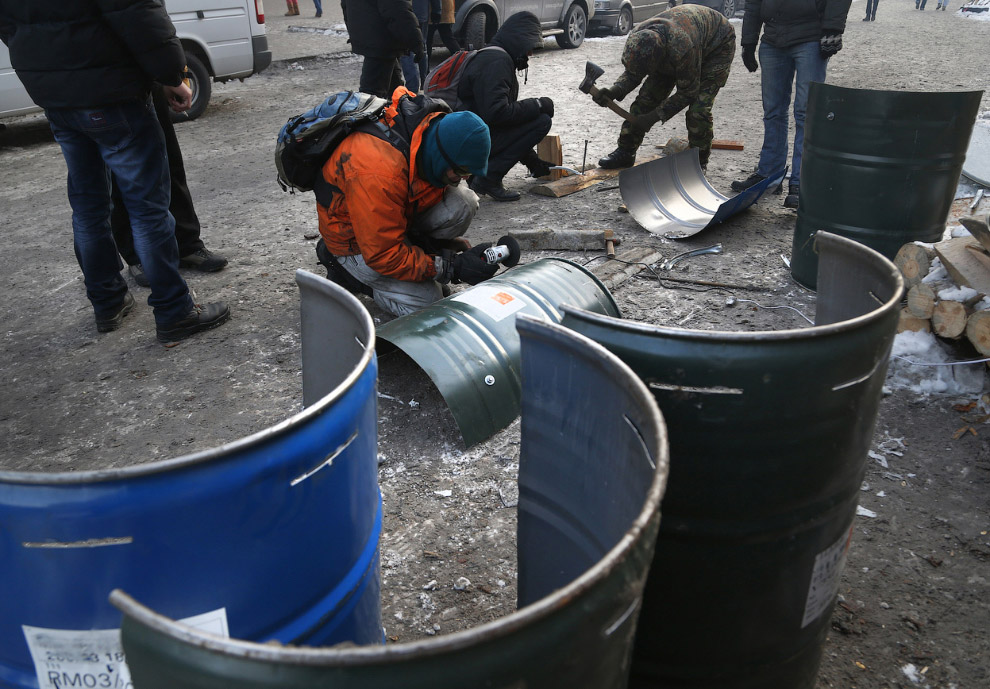Подготовка к боям с милицией. Группа молодых людей электропилами и топорами изготавливают щиты из металлических бочек