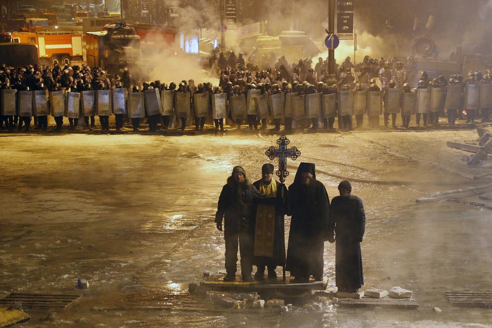 Представители церкви против беспорядков на улицах Киева, стоят между спецназом и радикалами. На асфальте виден лен, образовавшийся от применения водометов для разгона воинствующей толпы