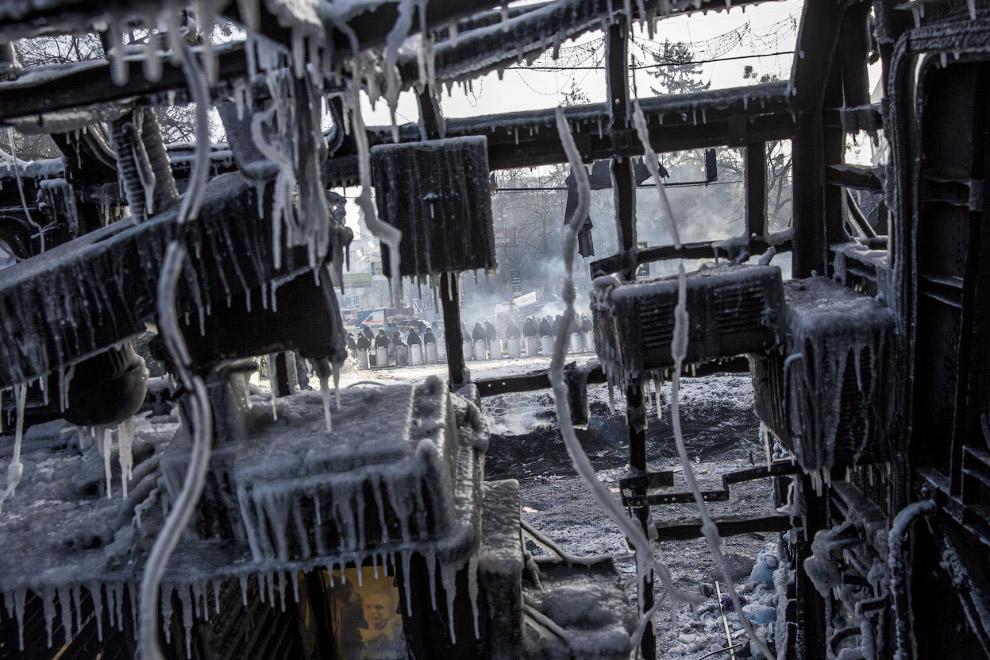 Вид сквозь остатки сгоревшего и облитого водой автобуса