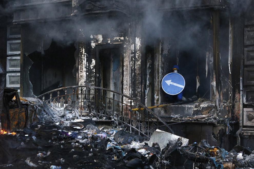 Обгоревшее здание и протестующий с дорожным знаком в качестве щита