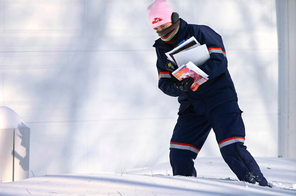 Работник Почты России почтовой службы США пробирается к клиентам против ветра, штат Иллинойс