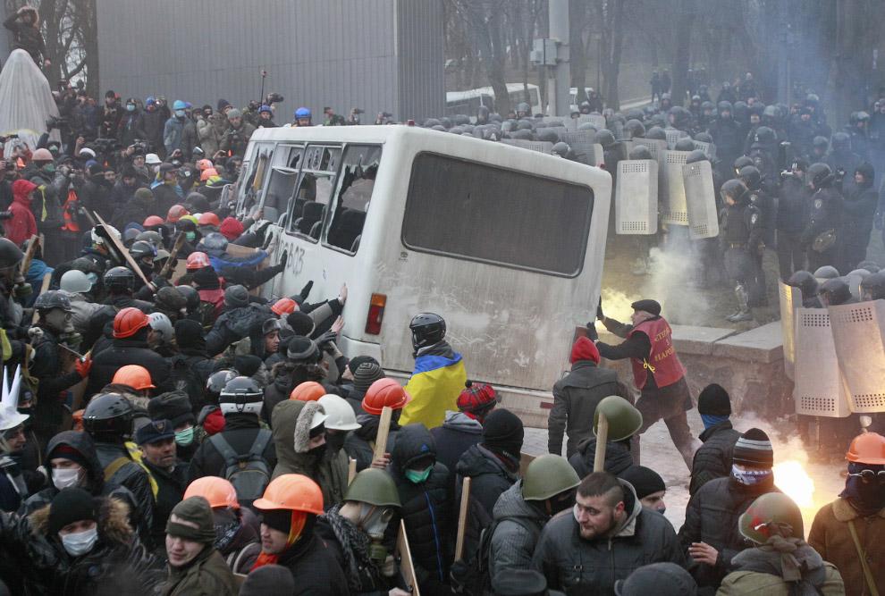 Протестующие переворачивают полицейский фургон во время митинга возле правительственных зданий в центре Киева