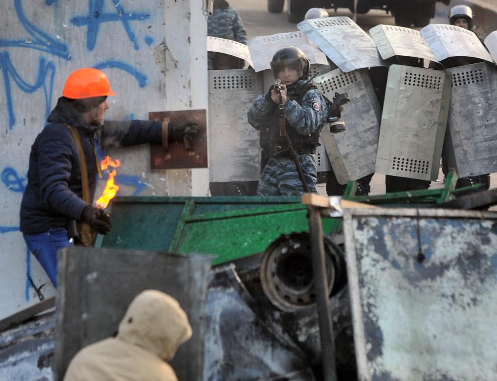 Протестующий готовится к броску коктейлем Молотова в полицейского