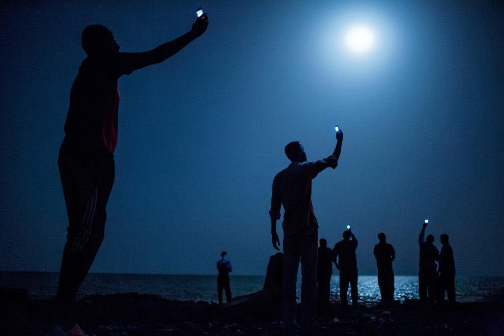 Африканские мигранты на ночном берегу города Джибути пытаются поймать сигнал, чтобы связаться с родственниками из соседнего Сомали по сотовому