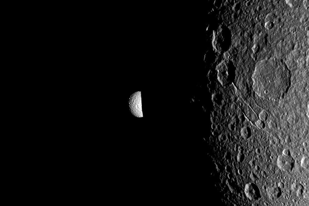 Спутник Мимас выглядывает из-за ночной стороны большого спутника Дионы