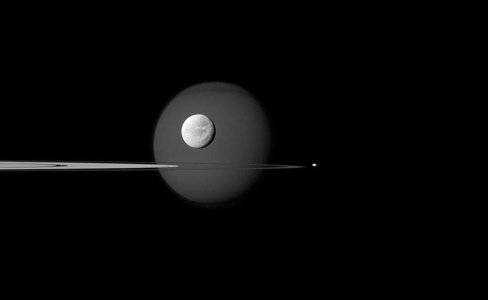 4 спутника. На заднем плане — огромный Титан, на его фоне — спутник Диона, справа — Пандора, еле заметная точка слева — спутник Пан