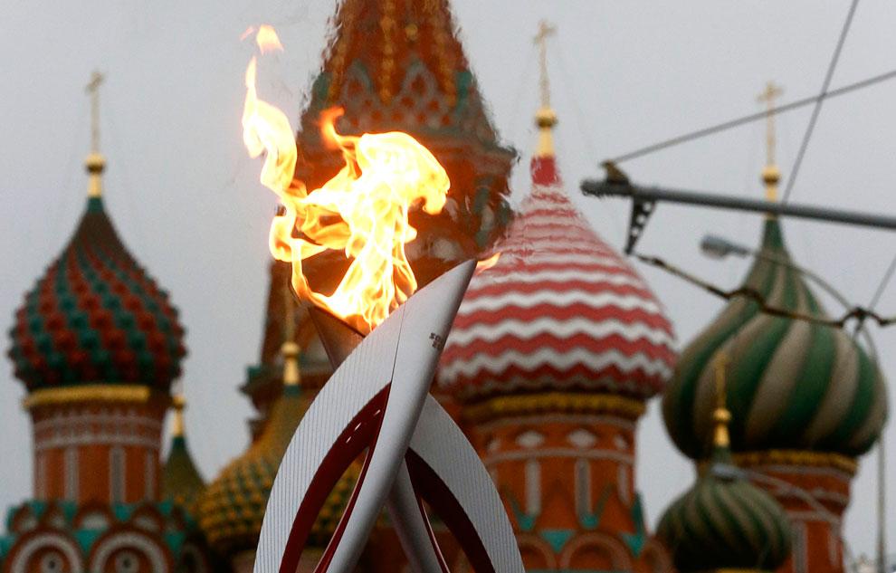 Передача Олимпийского огня на фоне собора Василия Блаженного во время эстафеты в Москве