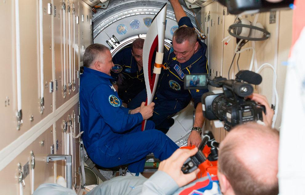 Факел держит в космическом пространстве русский космонавт Олег Котов