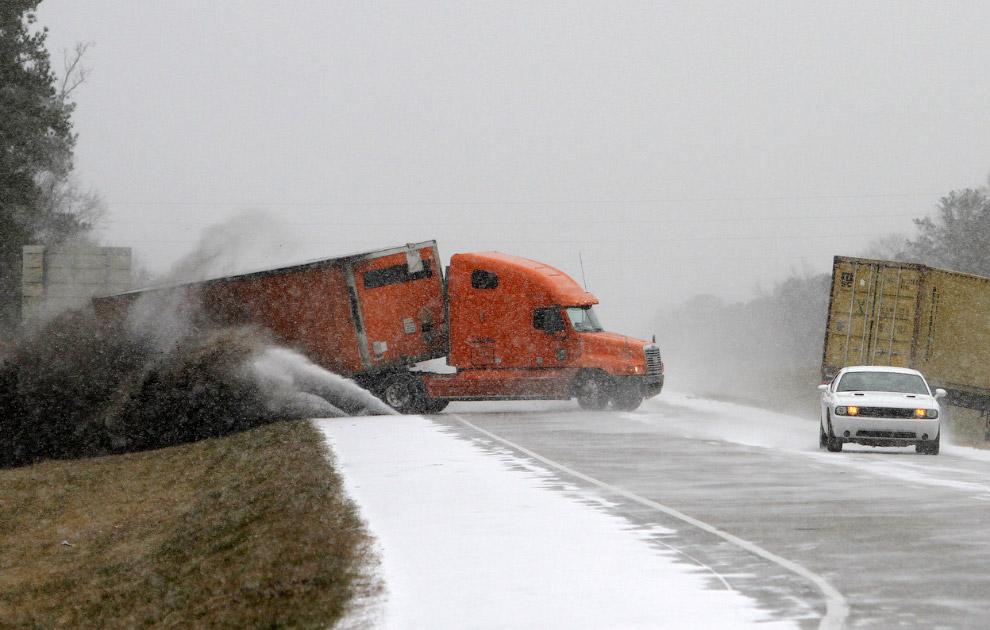 Это Алабама, 28 января 2014. Фотограф поймал момент, когда водитель оранжевого грузовика слетает с трассы